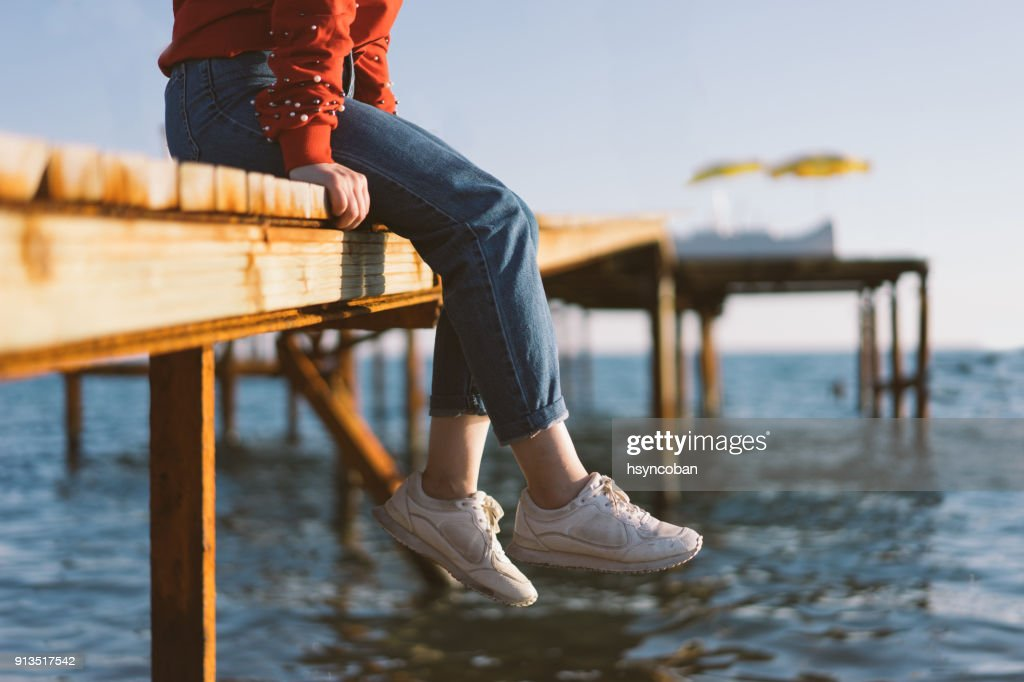 Woman's feet dangle from wooden wharf, above sea : Stock Photo