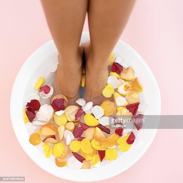 a woman's feet in a bowl of water and flower petals - black pedicure fotografías e imágenes de stock