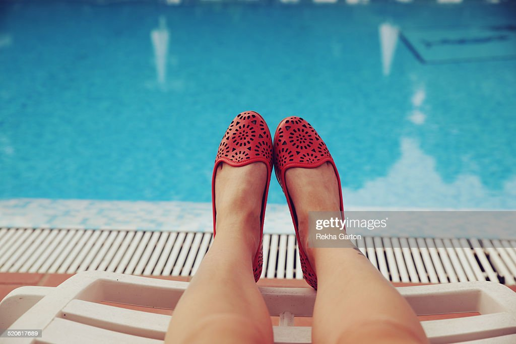Woman`s feet in front of a pool
