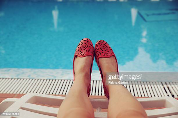 Woman's feet in front of a pool