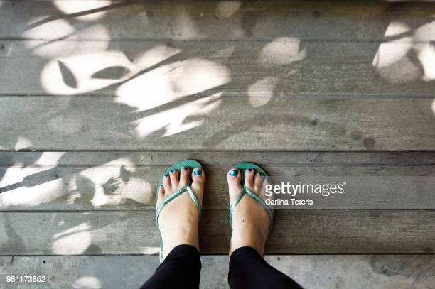 woman's feet in sandles and black leggings on a wooden floor - open toe stock pictures, royalty-free photos & images