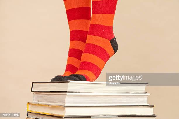 Woman's Feet in stripy socks standing on stack of books