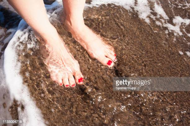 woman?s feet in waves at beach - wading stock pictures, royalty-free photos & images