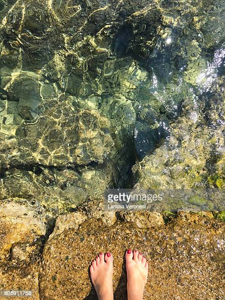 Woman's feet on a rocky beach on the island of Losinj, Croatia