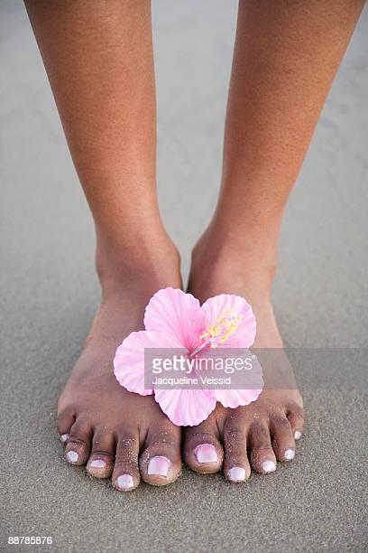 woman's feet on beach with flower - black pedicure fotografías e imágenes de stock