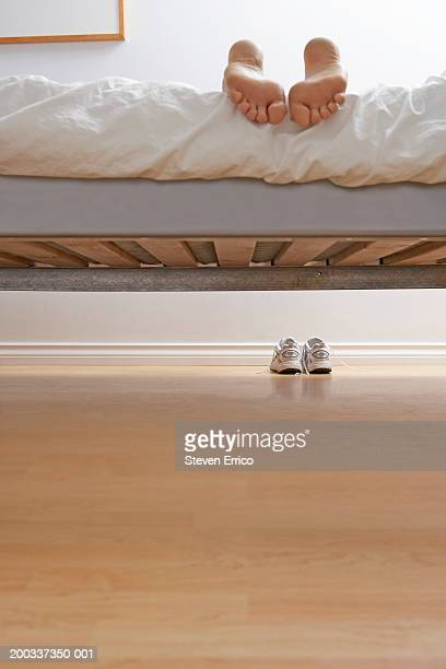 woman's feet on edge of bed, shoes on floor, view from under bed - woman lying on stomach with feet up stock photos and pictures