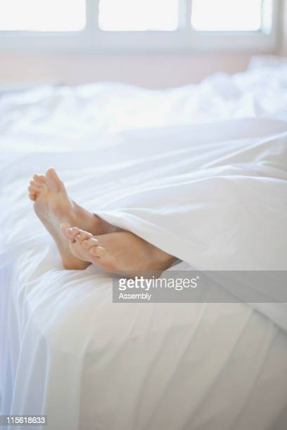 Woman's feet on end of bed