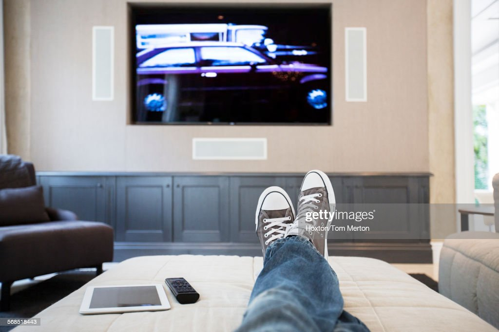 Womans feet on ottoman watching TV : Stock Photo