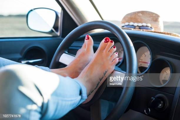 Woman's feet on the steering wheel