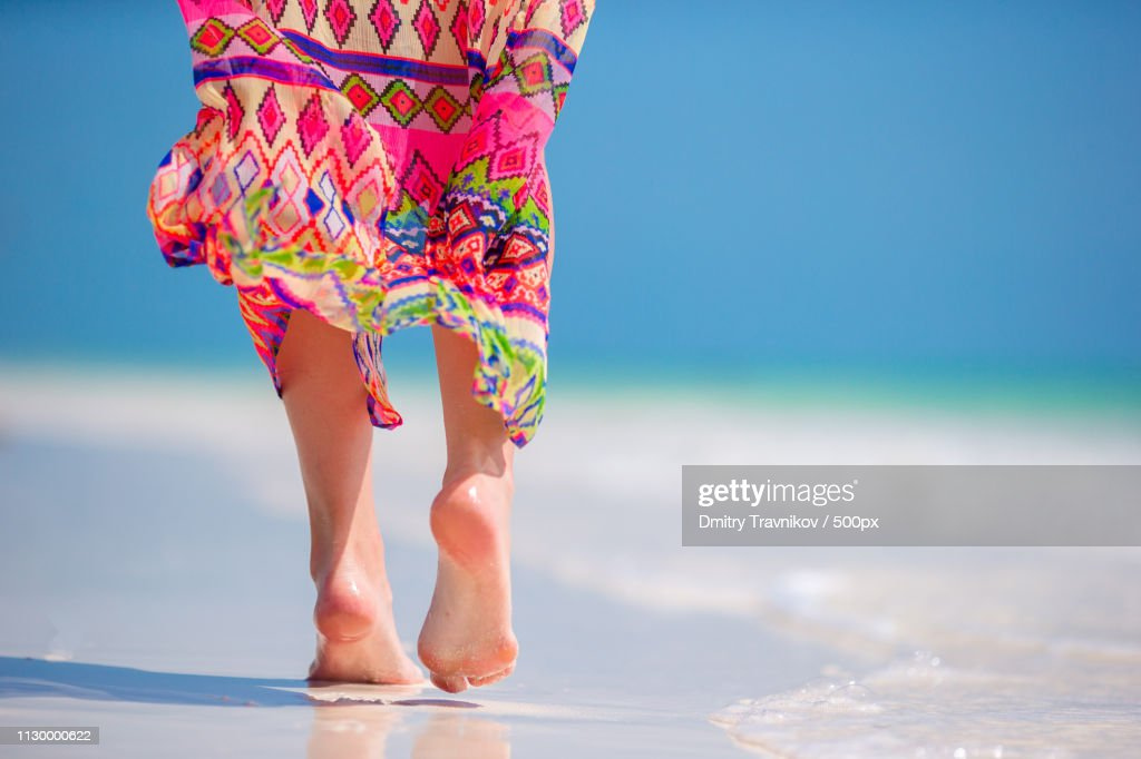 Woman's Feet On The White Sand Beach In Shallow Water : Stock Photo