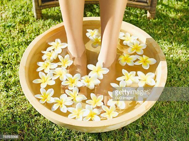 a woman's feet soaking in a bowl of water and flowers - genot stockfoto's en -beelden