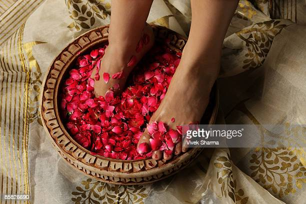 woman's feet soaking in rose petals and rose water - indian female feet stock pictures, royalty-free photos & images