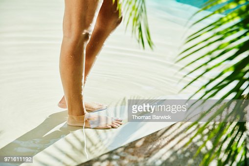 Womans feet standing in pool surrounded by palm fronds