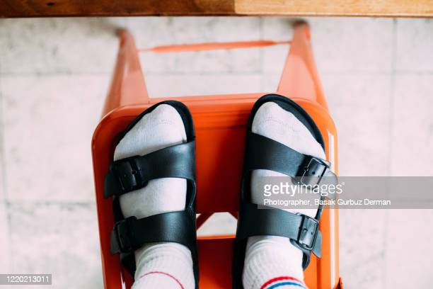 woman's feet, standing on metal stool - slipper stock pictures, royalty-free photos & images