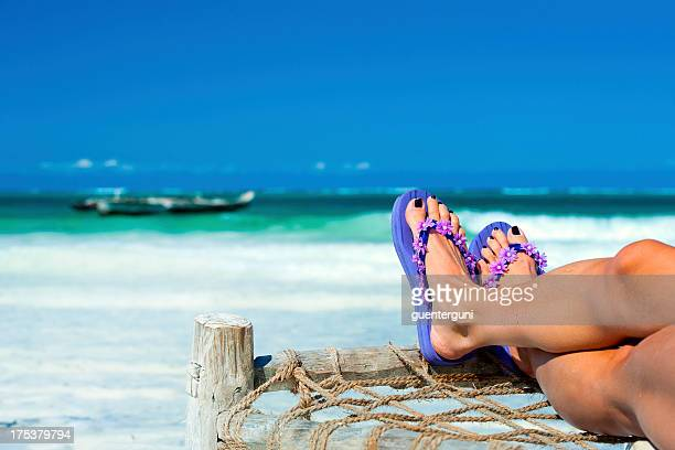 Womans feet with flip-flops at the beach