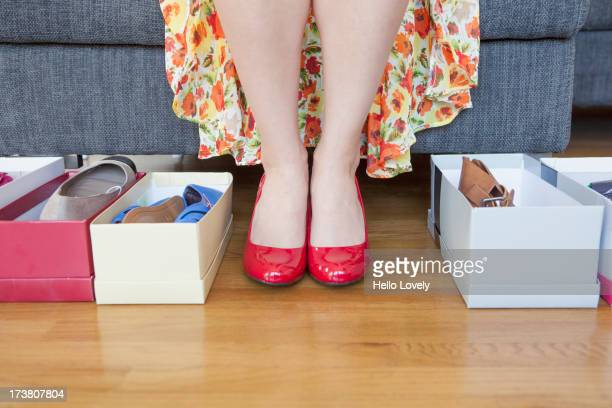 Woman's feet with shoe boxes on floor