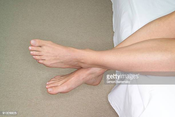 womans feet,legs hanging over side of bed - hanging stock pictures, royalty-free photos & images