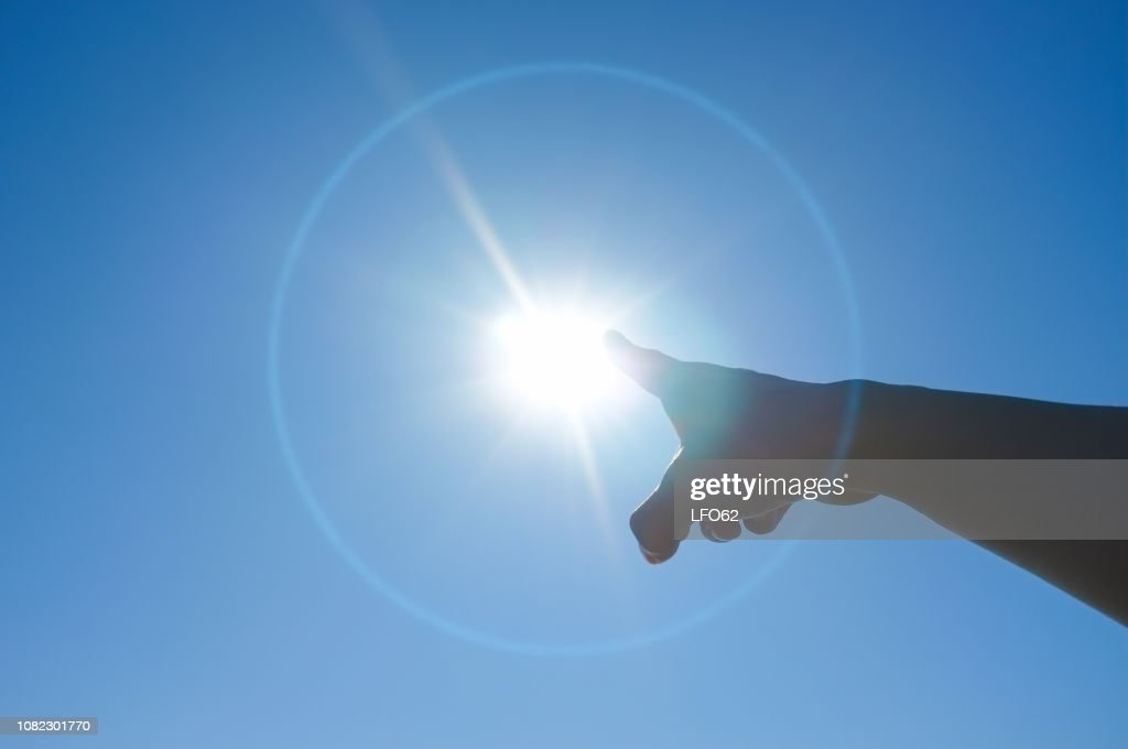 Woman's finger pointing to the sun : Stock Photo