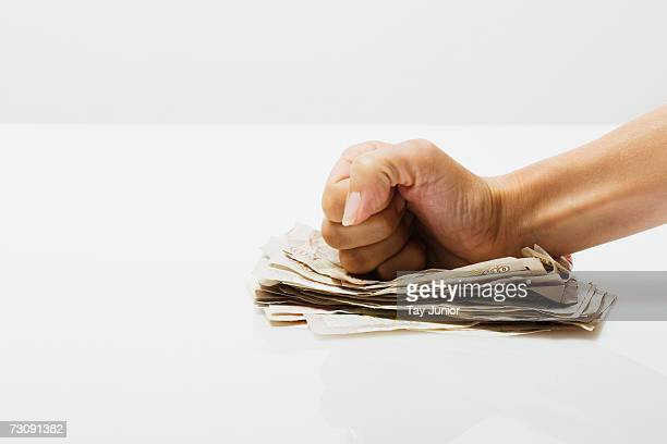 Woman's fist on pile of banknotes