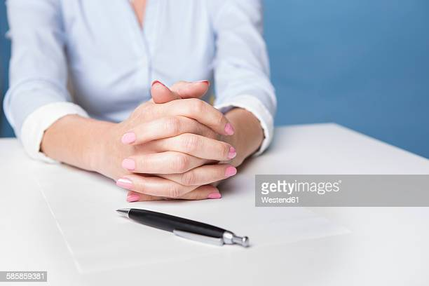 Womans folded hands on a sheet of paper