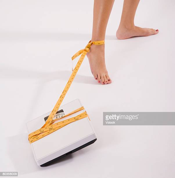 Woman's foot tied to scale with tape measure
