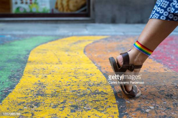a woman's foot with sandals and a rainbow flag tied to the knuckle making a step forward on a colored painted surface - サンダル ストックフォトと画像