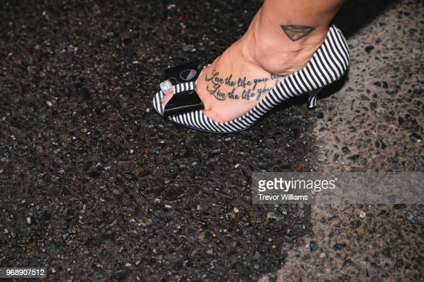 Woman's foot with tattoo in a high heel shoe