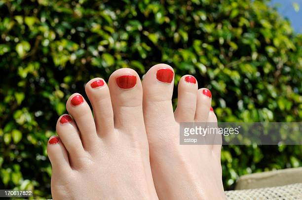 woman's fresh red pedicure with green bush in the background - pretty toes and feet stock photos and pictures