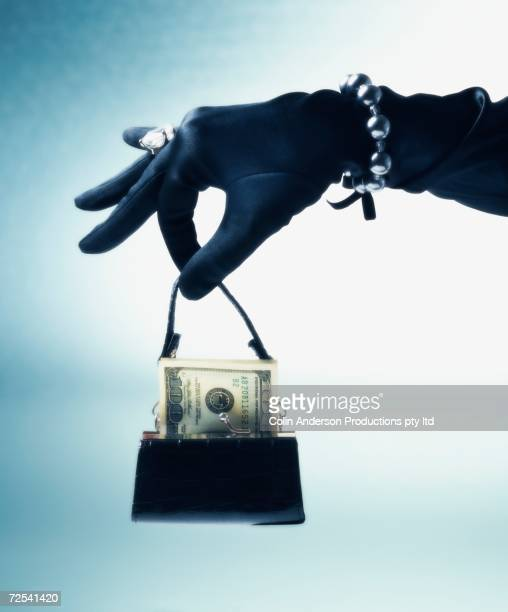 Woman's gloved and jeweled hand holding purse with US hundred dollar bill