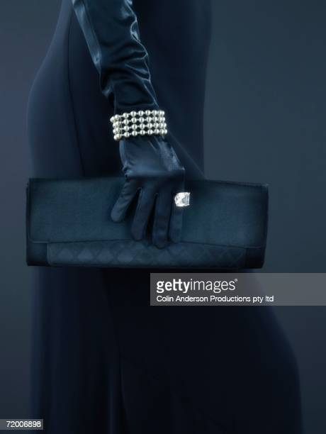 Woman's gloved hand with jewelry and handbag