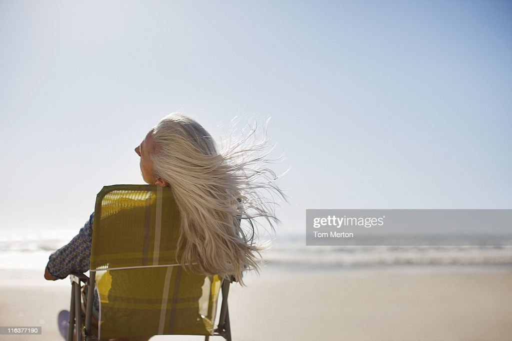Womans hair blowing in wind on beach : Stock Photo