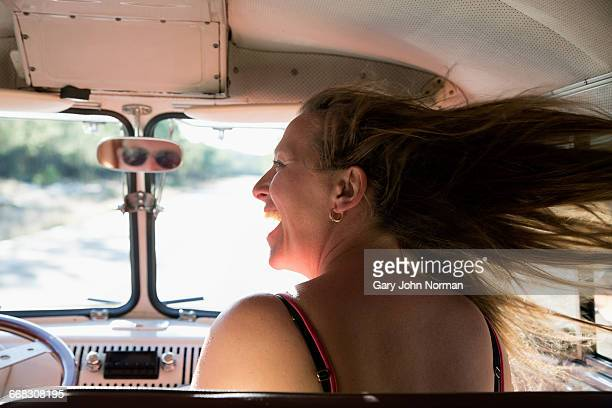 Woman's hair blowing out window of campervan