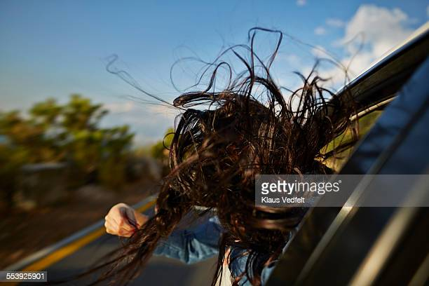 Womans hair blowing with head out of car window