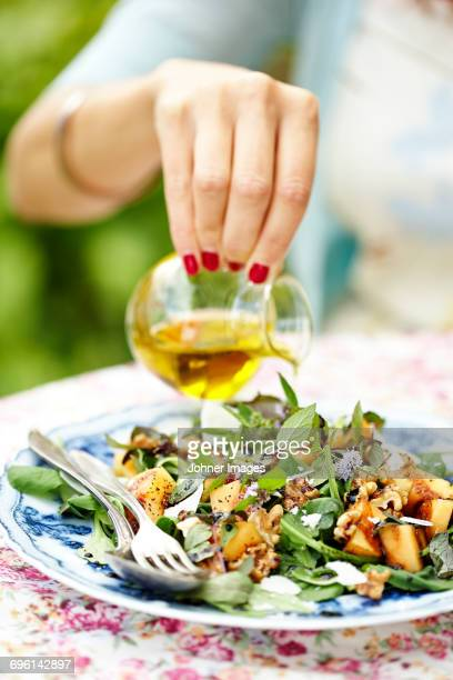 Womans hand adding oil into salad