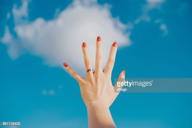 Woman's hand against blue sky and white clouds