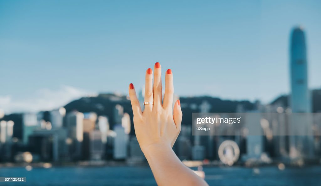 Woman's hand against iconic skyline of Hong Kong Victoria Harbour : Stock Photo