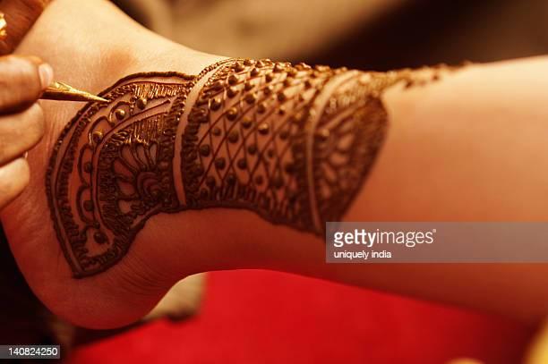 Woman's hand applying henna on bride's hand