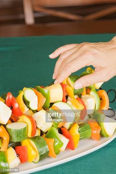 woman's hand arranging vegetable kebab skewers - vegetable kebab stock pictures, royalty-free photos & images