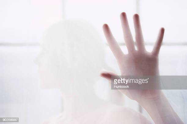 Woman's hand behind translucent glass