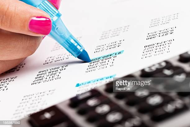 Mano de mujer cuidado de las cifras en un documento financiero