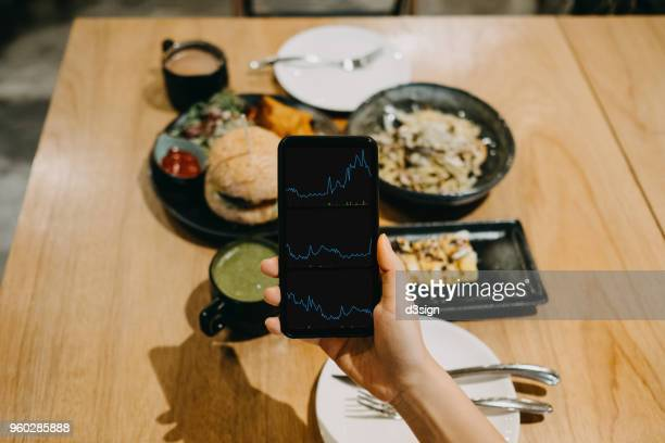 woman's hand checking financial data on smartphone while having meal in a restaurant - food staple stock pictures, royalty-free photos & images