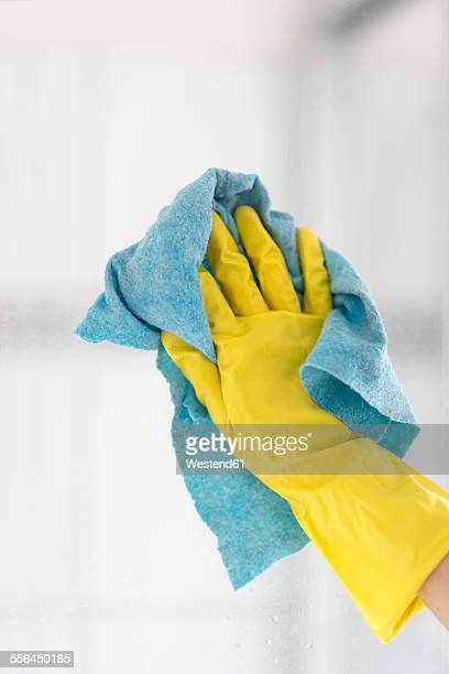 Womans hand cleaning glass pane