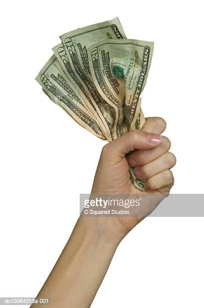 Woman's hand clutching 20 dollar bills on white background