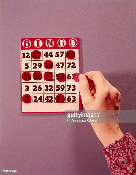 Woman's hand crossing off final number on Bingo card