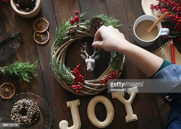 Womans hand decorating Christmas wreath on wooden table
