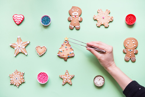 Woman's hand decorating Gingerbread cookies - gettyimageskorea