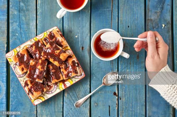 woman's hand dispersing sugar into cup of tea - ティースプーン ストックフォトと画像