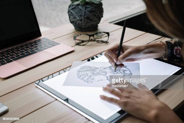 Womans hand drawing template on light table