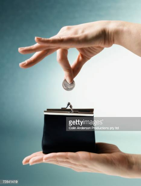 Woman's hand dropping coin into change purse