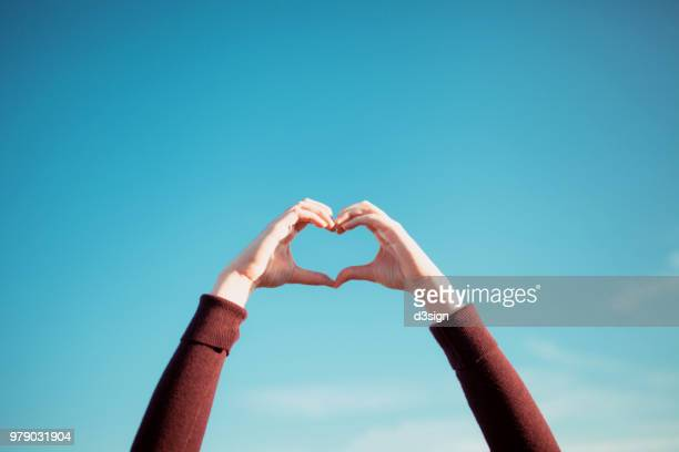 woman's hand gesturing a heart shape over clear blue sky and warm sunlight - solidarité photos et images de collection